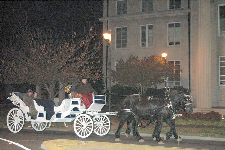A couple takes a ride in the back of a horse wagon