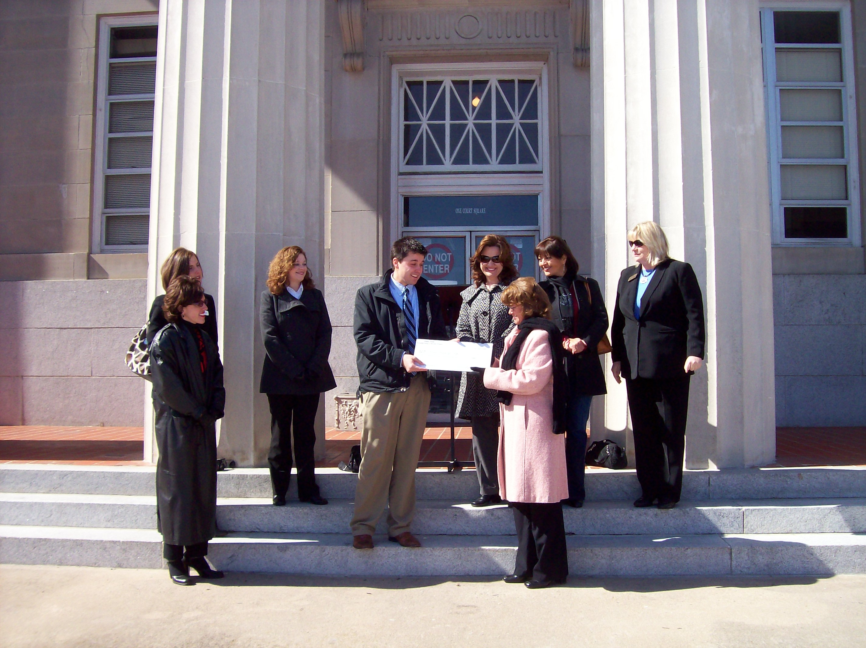 A group presents man with a check on steps