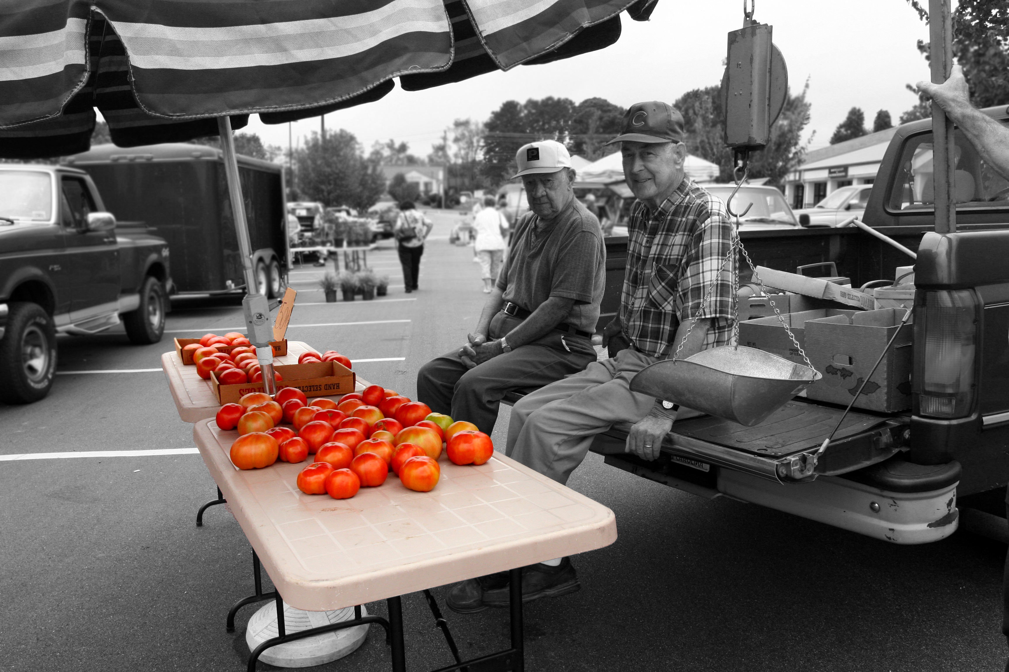 Farmer sits in front of tomatoes at Famer Market