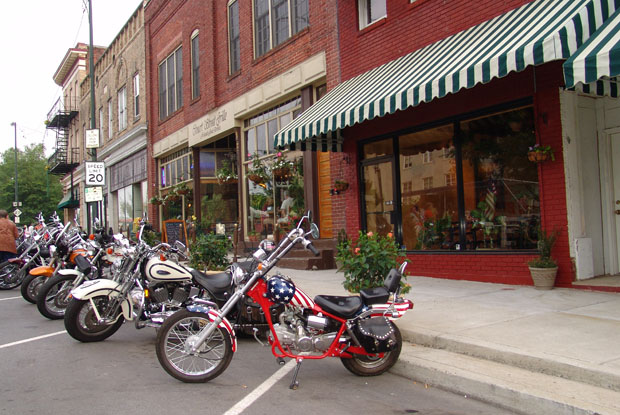 Motorcycles sit in front of local shops