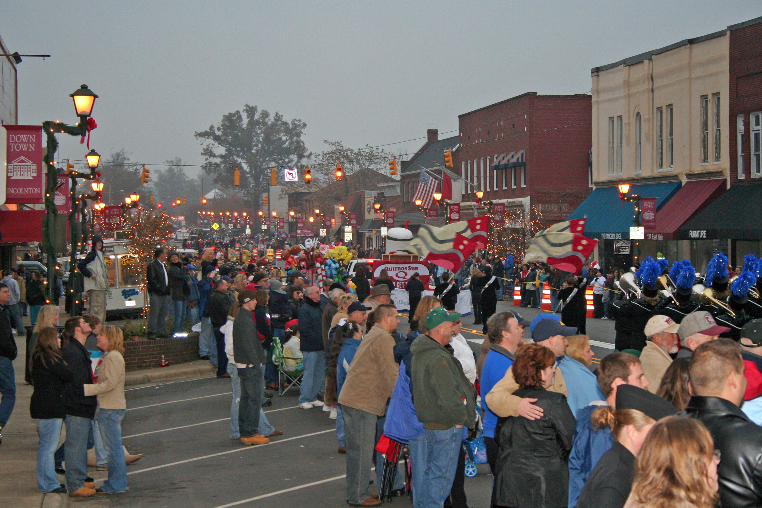 People gather for a parade on a foggy day